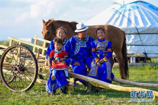 """呼日查毕力格(右二)与家人坐在勒勒车前合影(7月20日摄)。 今年35岁的呼日查毕力格是内蒙古赤峰市巴林左旗查干哈达苏木的牧民。从小喜欢蒙古马的他经过20年的努力,使自家的马群不断壮大,从最初的1匹发展到如今的100多匹。现阶段呼日查毕力格把主要精力放在了培养优秀的蒙古赛马上,这样既可以有较高的收入,又能够让蒙古马得到更多人的认可。 2018年3月,呼日查毕力格在自己的家乡查干哈达苏木创建了""""黑骏马旅游度假营""""。在他的度假营中,游客可以亲身参与到挤马奶、骑马、打马印、剪马鬃等丰富多彩的马文化体验项目中,深入了解蒙古马独特的生活习性和特点。 新华社记者 彭源 摄"""