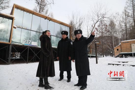 """图为民警与""""雪城义警""""分队在观察点勘察(韩志祺摄)"""
