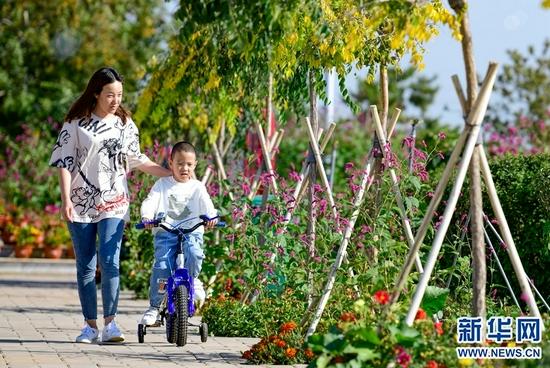 9月14日,游客在位于伊金霍洛旗纳林陶亥镇的鄂尔多斯市乌兰集团荣恒煤矿采煤复垦区公园里游玩。新华网 发(王正 摄)