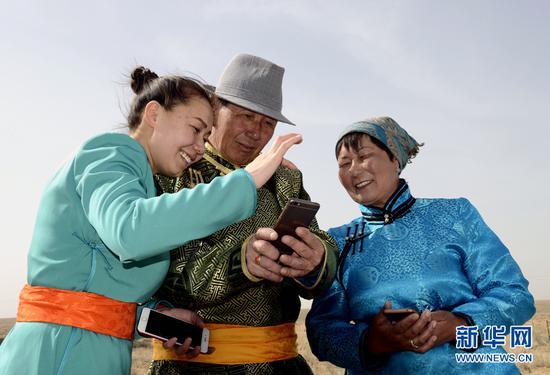 图为牧民巴拉图苏和与妻子和女儿一起欣赏自己拍摄的作品。