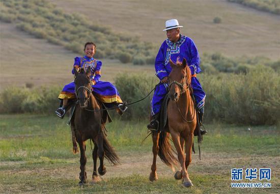 """呼日查毕力格教女儿骑马(7月20日摄)。 今年35岁的呼日查毕力格是内蒙古赤峰市巴林左旗查干哈达苏木的牧民。从小喜欢蒙古马的他经过20年的努力,使自家的马群不断壮大,从最初的1匹发展到如今的100多匹。现阶段呼日查毕力格把主要精力放在了培养优秀的蒙古赛马上,这样既可以有较高的收入,又能够让蒙古马得到更多人的认可。 2018年3月,呼日查毕力格在自己的家乡查干哈达苏木创建了""""黑骏马旅游度假营""""。在他的度假营中,游客可以亲身参与到挤马奶、骑马、打马印、剪马鬃等丰富多彩的马文化体验项目中,深入了解蒙古马独特的生活习性和特点。 新华社记者 彭源 摄"""