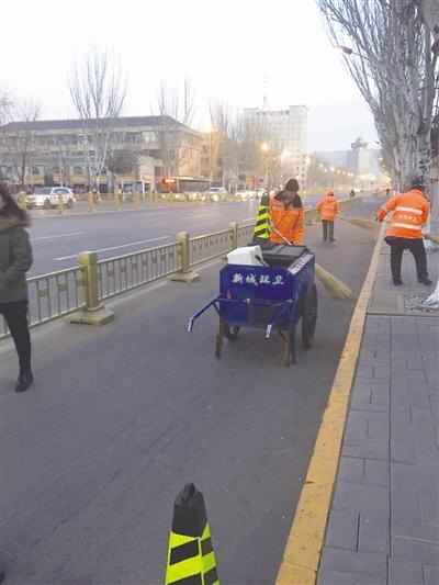 环卫工人用推车和安全锥桶保障作业安全