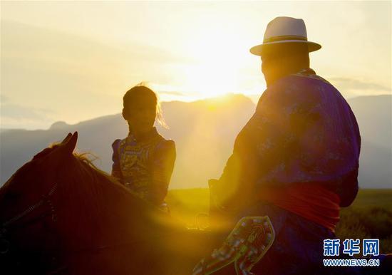 """夕阳下,呼日查毕力格在教女儿骑马(7月20日摄)。 今年35岁的呼日查毕力格是内蒙古赤峰市巴林左旗查干哈达苏木的牧民。从小喜欢蒙古马的他经过20年的努力,使自家的马群不断壮大,从最初的1匹发展到如今的100多匹。现阶段呼日查毕力格把主要精力放在了培养优秀的蒙古赛马上,这样既可以有较高的收入,又能够让蒙古马得到更多人的认可。 2018年3月,呼日查毕力格在自己的家乡查干哈达苏木创建了""""黑骏马旅游度假营""""。在他的度假营中,游客可以亲身参与到挤马奶、骑马、打马印、剪马鬃等丰富多彩的马文化体验项目中,深入了解蒙古马独特的生活习性和特点。 新华社记者 彭源 摄"""