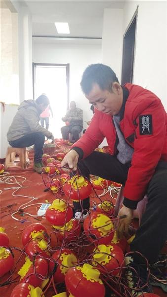 工人正在检查去年用过的彩灯