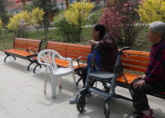 老人们坐在长椅上休息、聊天