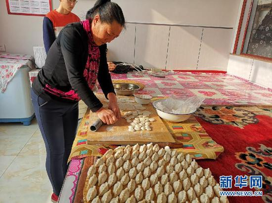 温艮忠的爱人正在包饺子。(新华网 杨腾格尔摄)