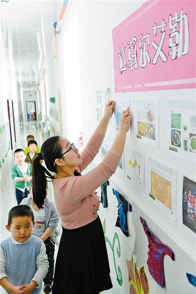 呼伦贝尔市鄂温克族自治旗西苏木诺图格幼儿园老师在宽敞明亮的教室布置板报