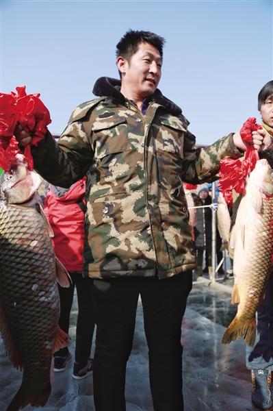 市民展示自己拍得的两条鱼