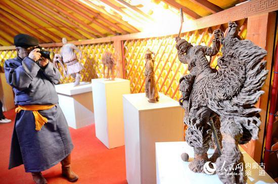 驼球泥塑前蒙古国游客拍照留念