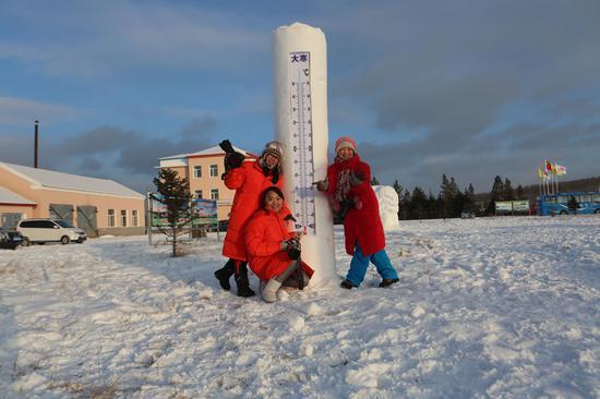 游客在根河冷极村雪雕前拍照留念