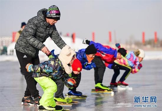 贾文超(左)指导小队员们滑冰的基本动作