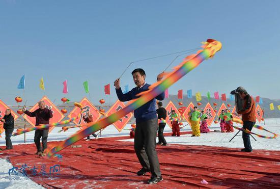 民间艺人在前窑子水库表演冰上空竹龙