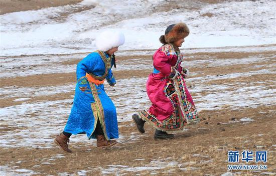 """两名身穿民族服饰的蒙古族儿童前往观看""""冰雪那达慕"""""""