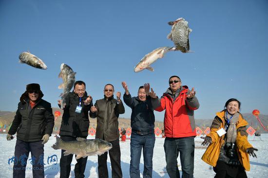 游客在前窑子水库的冰面上展示捕到的草鱼