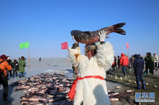 渔民捧起一条约20公斤重的青鱼(曹桢 摄)