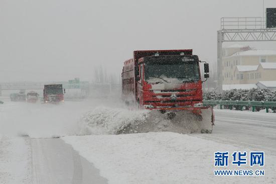 除雪车在高速公路上实施不间断除雪作业(罗杰 摄)