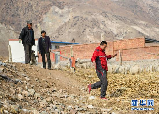 赵飞在土默特左旗向村民们打听完道路情况返回车上