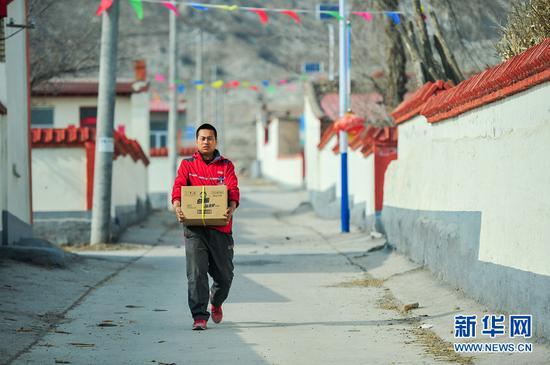 3月16日,赵飞在土默特左旗古雁村为客户配送包裹