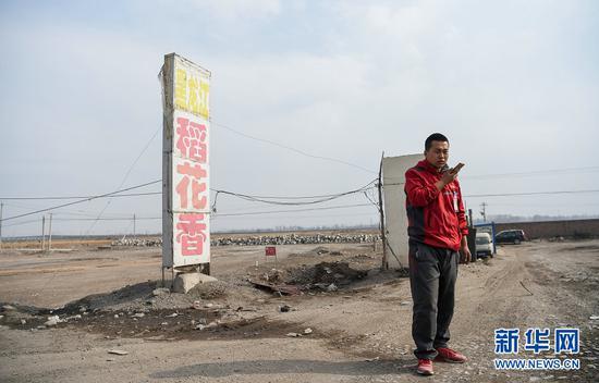 赵飞在土默特左旗一条公路旁等待客户来取包裹