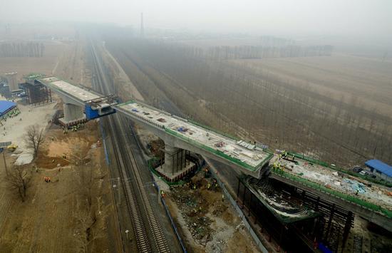 3月17日,由中铁十四局集团参建的国家重点铁路项目——内蒙古通辽至辽宁新民北高铁全线首座转体桥成功转体,成为全线4座转体桥中首座成功转体的桥梁。此次大桥转体,标志着内蒙古连接东北地区的首条高铁建设取得阶段性突破,为下一步架梁和全线铺轨节点目标按期实现打下坚实的基础。 (内蒙古日报社融媒体记者 梁亮 摄)