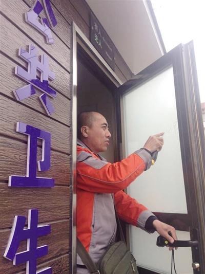 工作人员在清理公厕门上的乱涂乱画