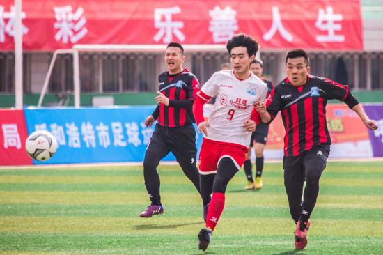 草原雄鹰足球队与武川县足球队的球员在比赛中。