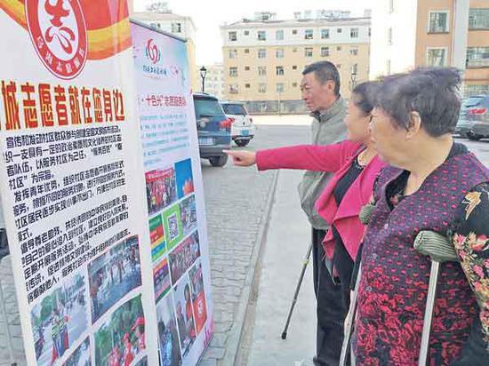 社区居民观看创城宣传展板