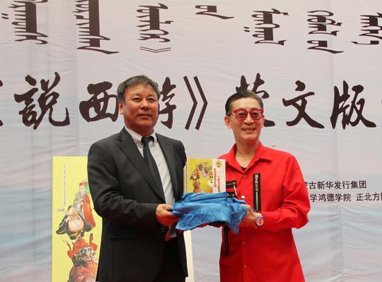 内蒙古日报社副总编辑乌日吐那斯图向章金莱先生(右一)转交100套《听孙悟空说西游》蒙文版图书。