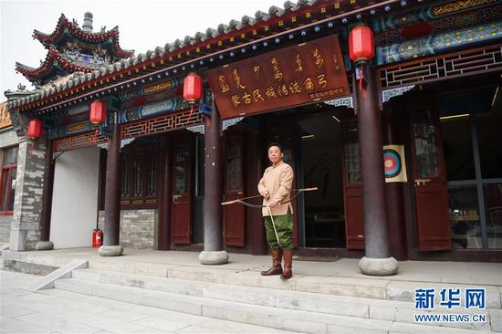 诺敏手持弓箭站在自己的传统角弓展厅前。