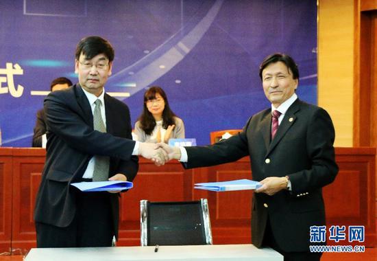 内蒙古大学文学与新闻传播学院副院长魏永贵(左)与新华社中国经济信息社内蒙古中心总经理、经济研究中心主任张润光签署战略合作协议
