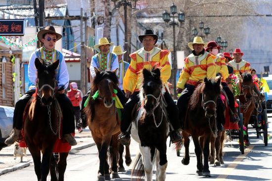 """俄罗斯族巴斯克传统节日中,男女老少们乘坐""""三套车""""欢庆节日。"""