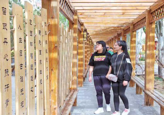 社会主义核心价值观主题园长廊内,挂满了传统文化标语牌,吸引了不少市民观看。
