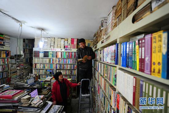 4月21日,段存瑞(右)和老伴一起打理古旧书店。