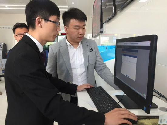 王超(左)在银行工作人员的指导下办理个体工商户电子营业执照
