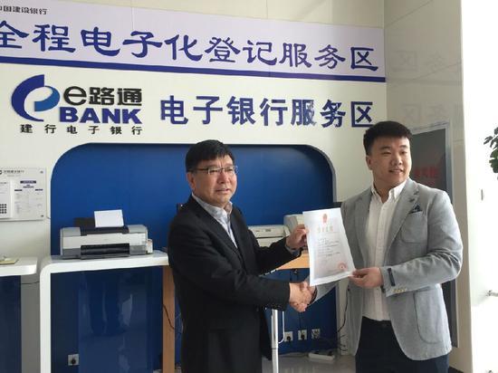 王超(右)拿到了全区首张个体工商户电子营业执照