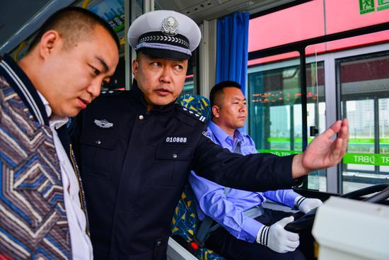 随车测试的警官正与公交公司的工作人员针对路况、速度等方面进行交流