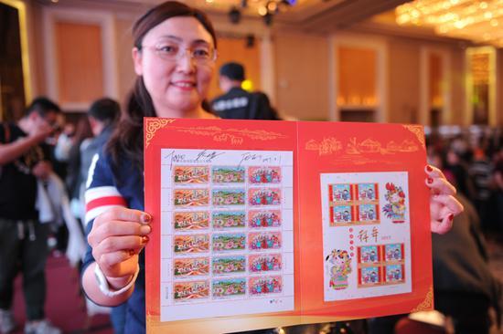 宋女士展示刚买到的邮票