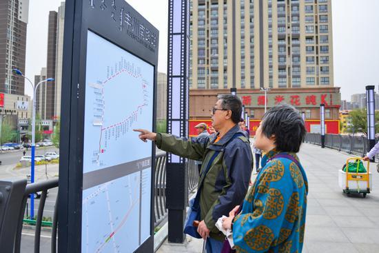 看到快速公交上了路,过往的市民停下脚步对天桥上的公交路线图研究了起来