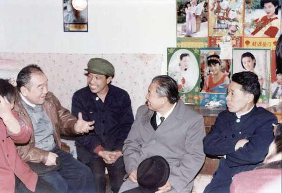 1991 年2 月,布赫同志(左一)与原海勃湾矿务局职工梁俊清一家亲切交谈。(神华乌海能源公司提供)