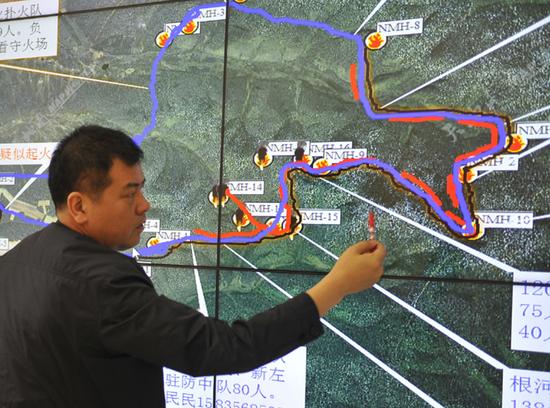 指挥部工作人员描述火场周边环境。内蒙古日报社融媒体记者 韩卿立 摄