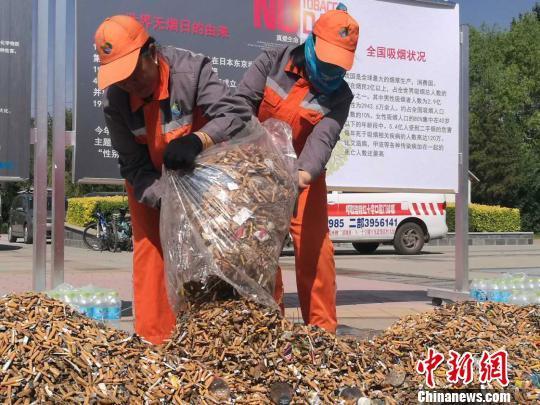环卫工人将捡拾来的烟头堆在一起。