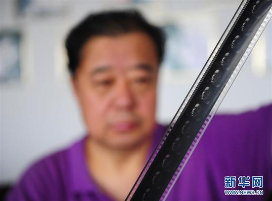 内蒙古电影博物馆创办人之一杨保华在检查老电影《地道战》的拷贝(6月10日摄)。