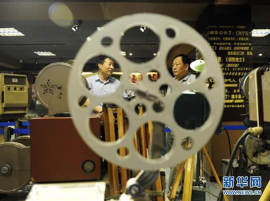 内蒙古电影博物馆创办人之一宋呼生(左)为参观者讲解老式放映机(6月10日摄)。