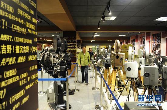内蒙古电影博物馆志愿者赵承英(前)在馆内巡视(6月10日摄)。