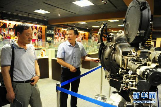 内蒙古电影博物馆创办人之一宋呼生(右)为参观者讲解老式放映机(6月10日摄)。