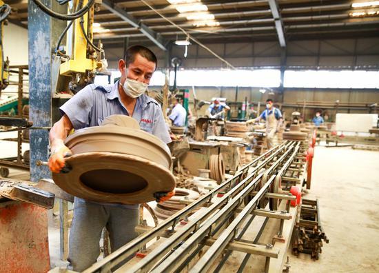 工人们正在用伴生粘土制作特高压瓷绝缘子。