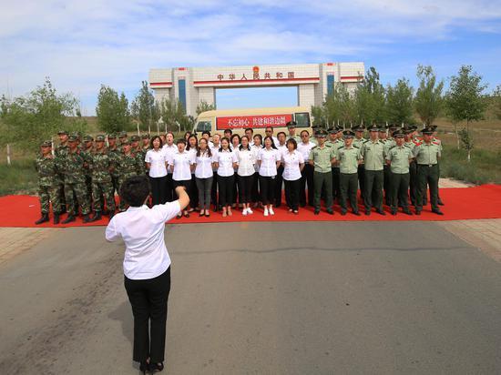 图为边检站党员官兵与学校党员在国门下共唱红歌