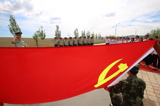 图为边检站党员官兵与学校党员面对党旗庄严宣誓