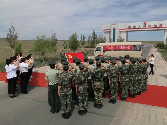 图为边检站党员官兵与学校党员在国门下面对党旗庄严宣誓