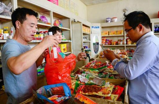 很多蒙古国的商人来到满都拉镇宝丰日用品超市购买货物,店主赵宝元夫妇是汉族人,却可以用流利的蒙语与他们交流。图为赵宝元正在为来自蒙古国的客人备货,值得一提的是,这位客人正在使用微信扫码支付货款。秦文秀摄
